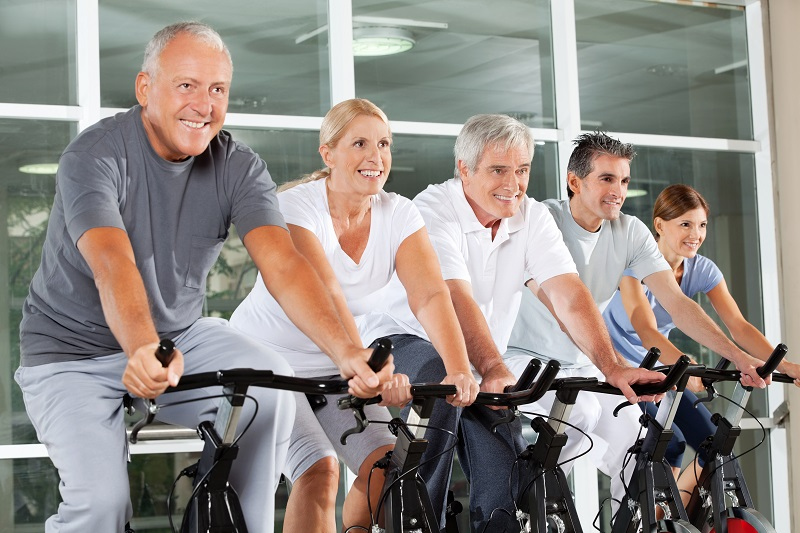 Happy senior citizens exercising in spinning class in fitness ce