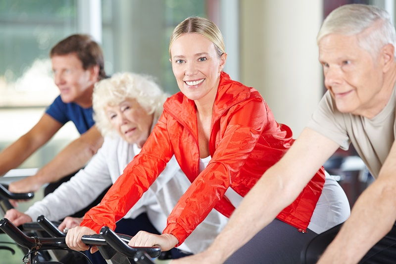 Elderly happy woman exercising in fitness center on a spinning b