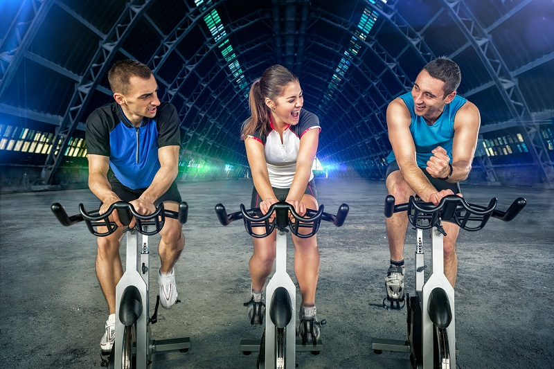 Young people  doing spinning on cycle bike