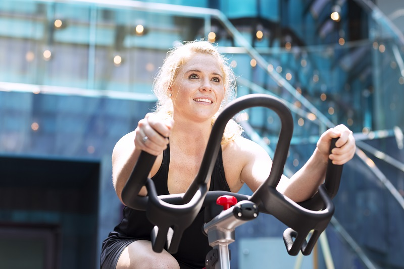 Young girl working out on stationary bicycle