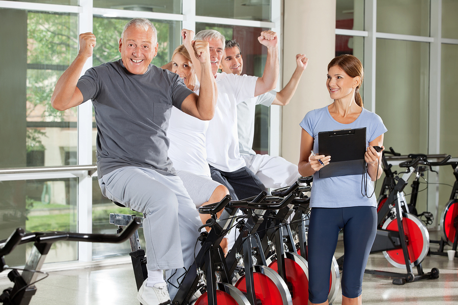 Cheering happy senior citizens with fitness trainer in gym