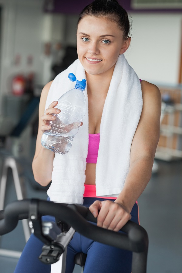 Portrait of a tired woman drinking water while working out at spinning class in gym