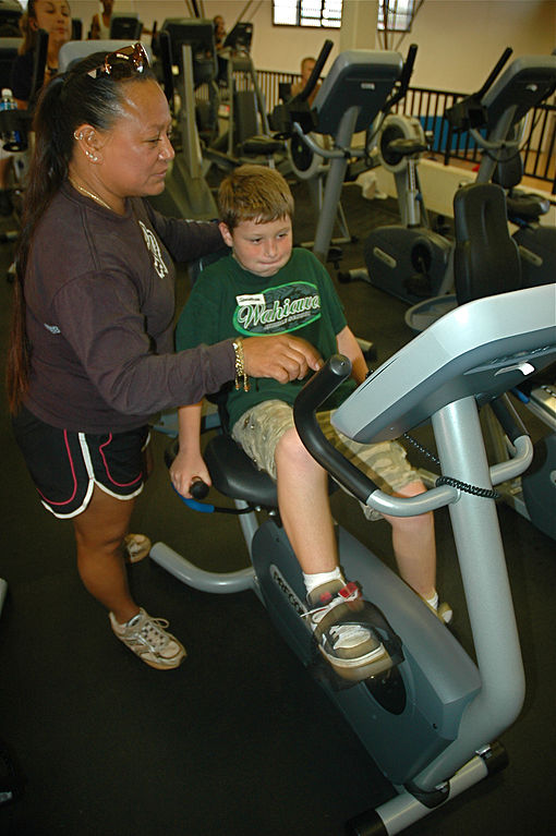 a boy trying out a recumbent bike with assistance of an older woman