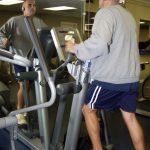 a man using an elliptical machine in front of a mirror