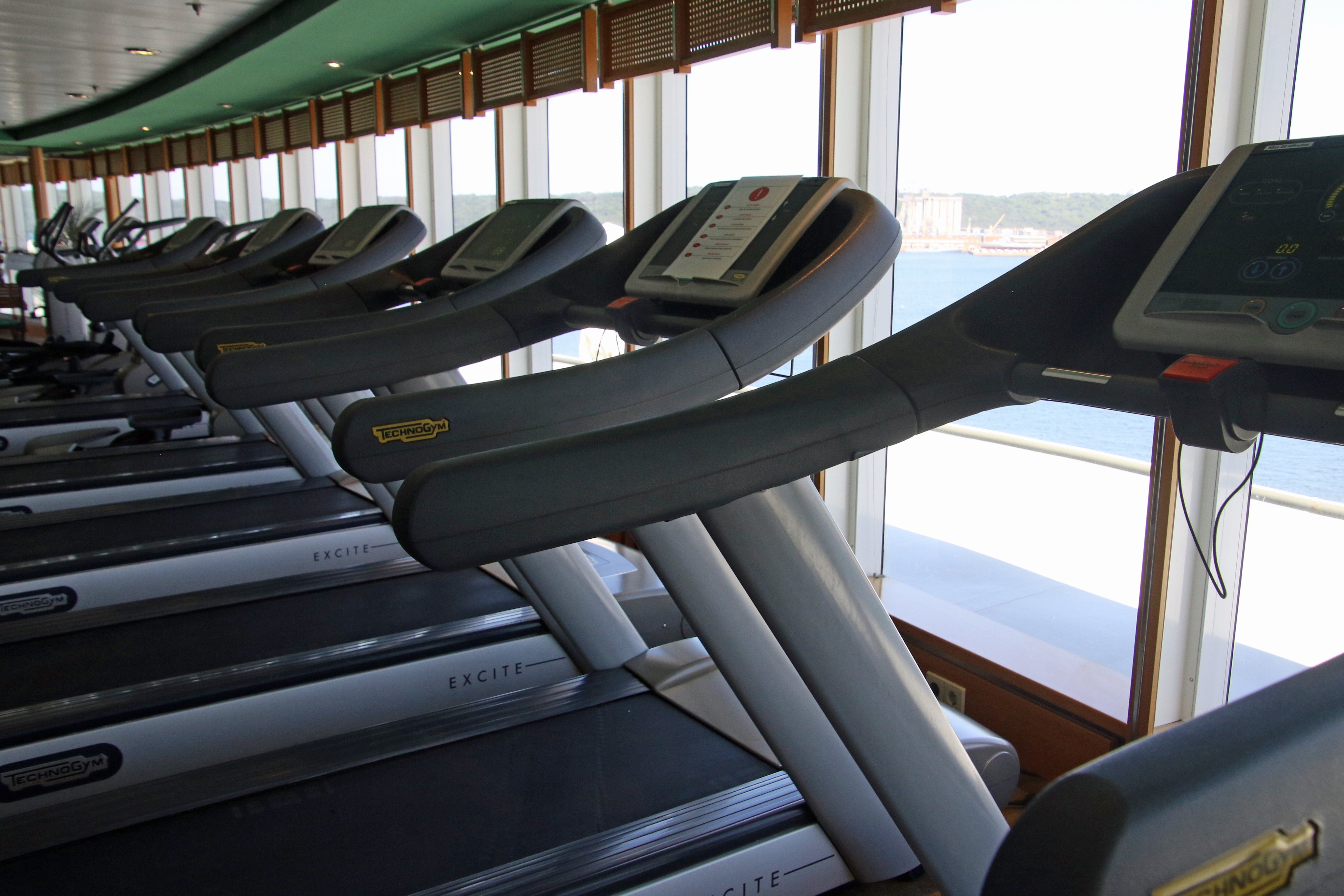 several treadmill machines facing the window in the gym