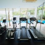 a gym studio equipped with treadmill machines, elliptical machine and a recumbent exercise bike and with a view of the swimming pool area