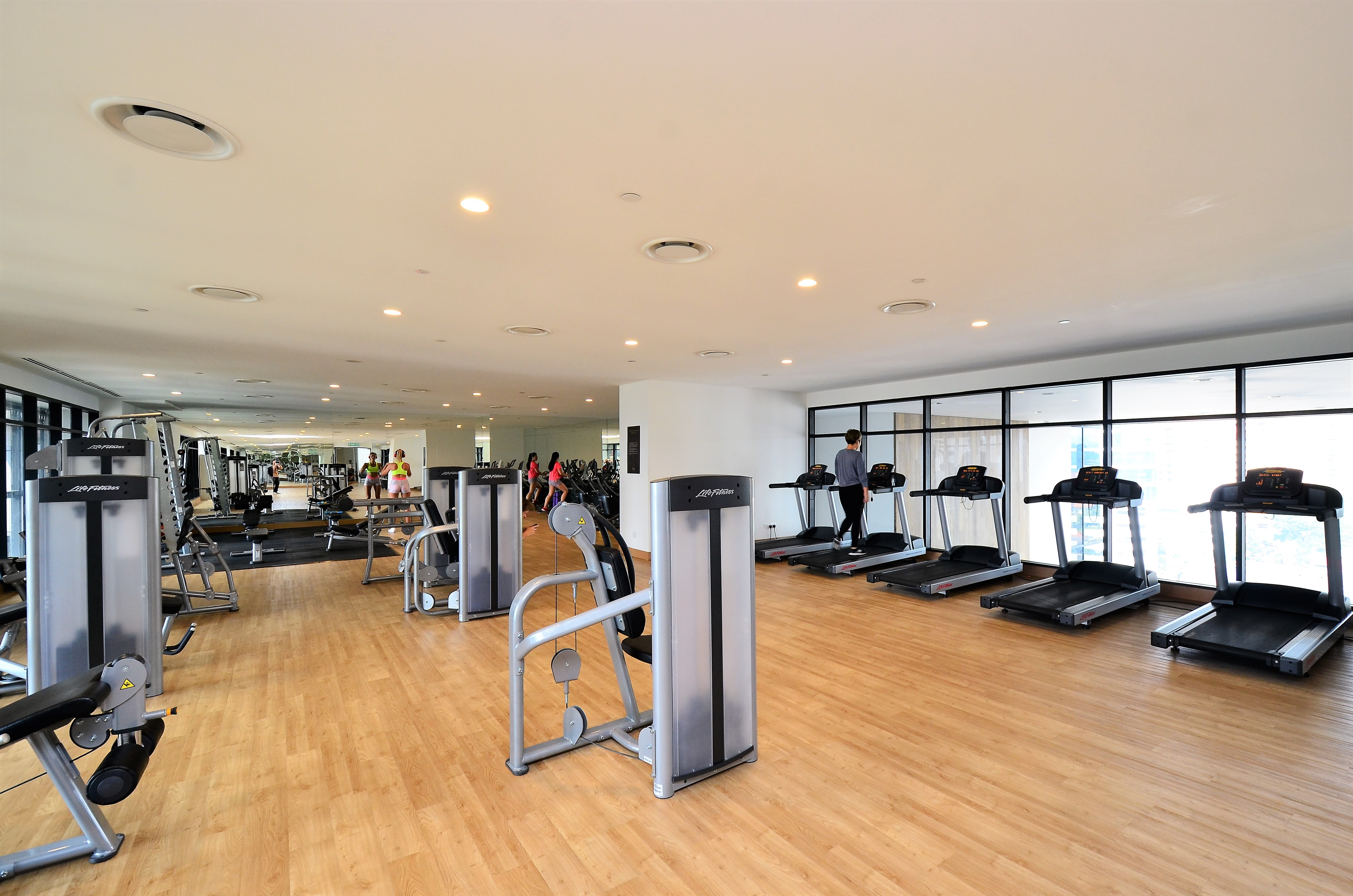 a spacious gym studio with treadmill and other gym equipment
