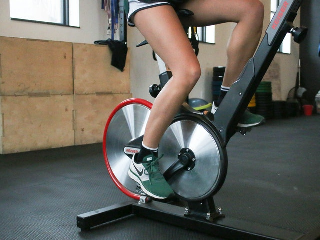woman using an upright bike while wearing indoor cycling shoes