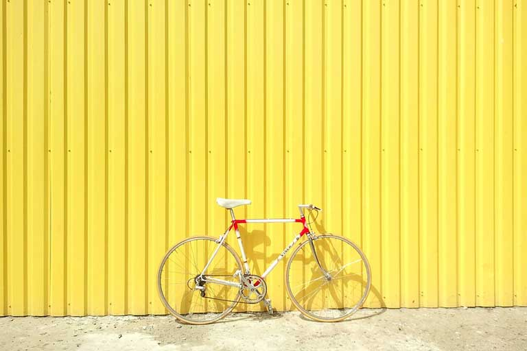 bike parked infront of yellow background