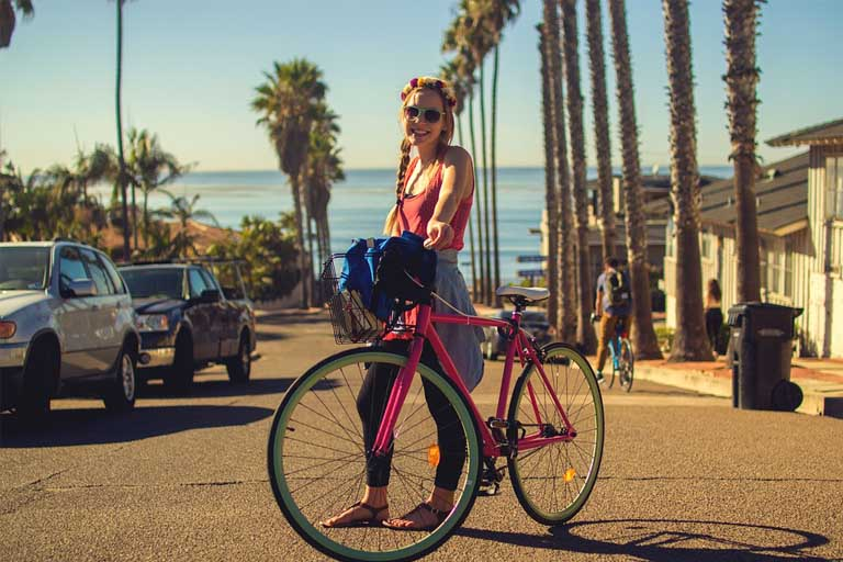 woman standing beside her pink bike