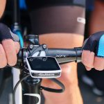 photo focused on hands of a biker wearing the best cycling gloves while riding a bicycle