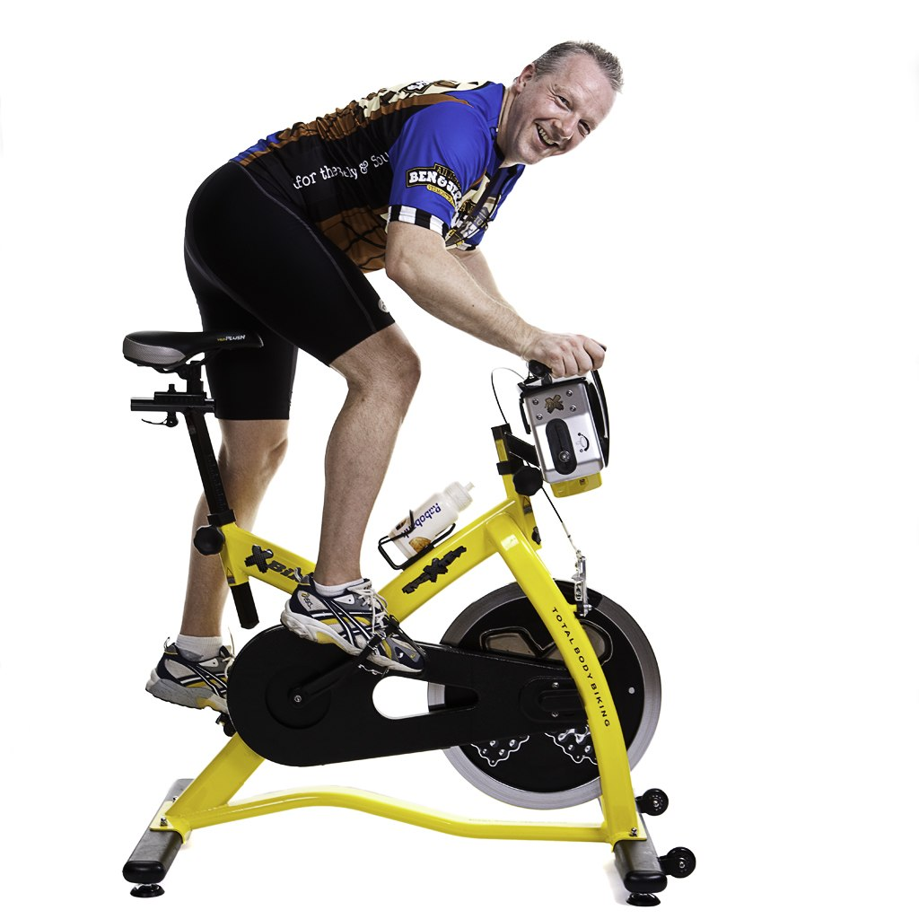 A man demonstrating how to do a spin bike workout routines for home