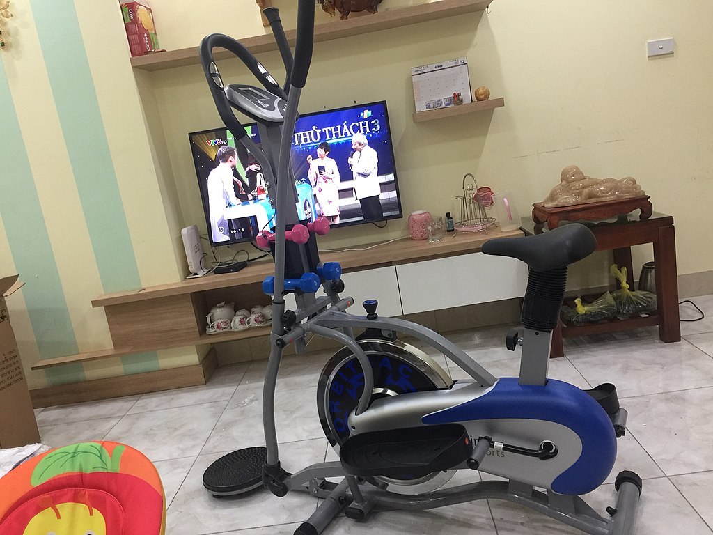 A spin bike in a living room in front of a tv