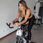 A girl doing a spin bike workout routines for home